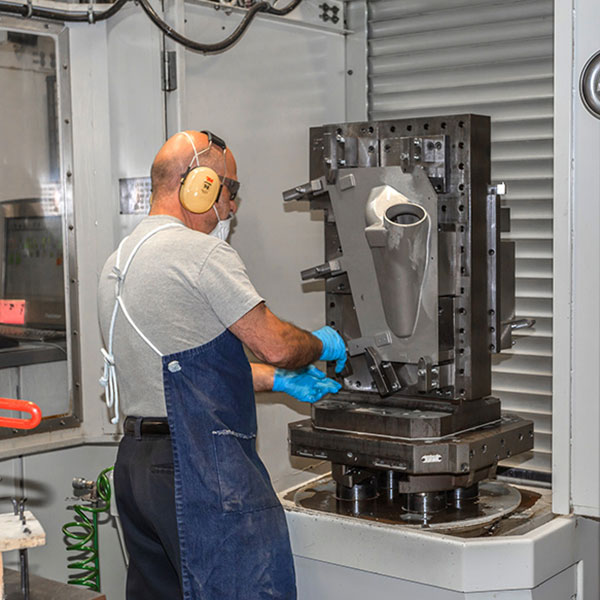 employee with yellow ear protection working in machining factory